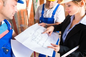 Construction site team or architect and builder or worker with h